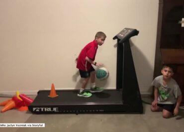 Chłopak trenuje kozłowanie piłką na ruchomej bieżni z przeszkodami